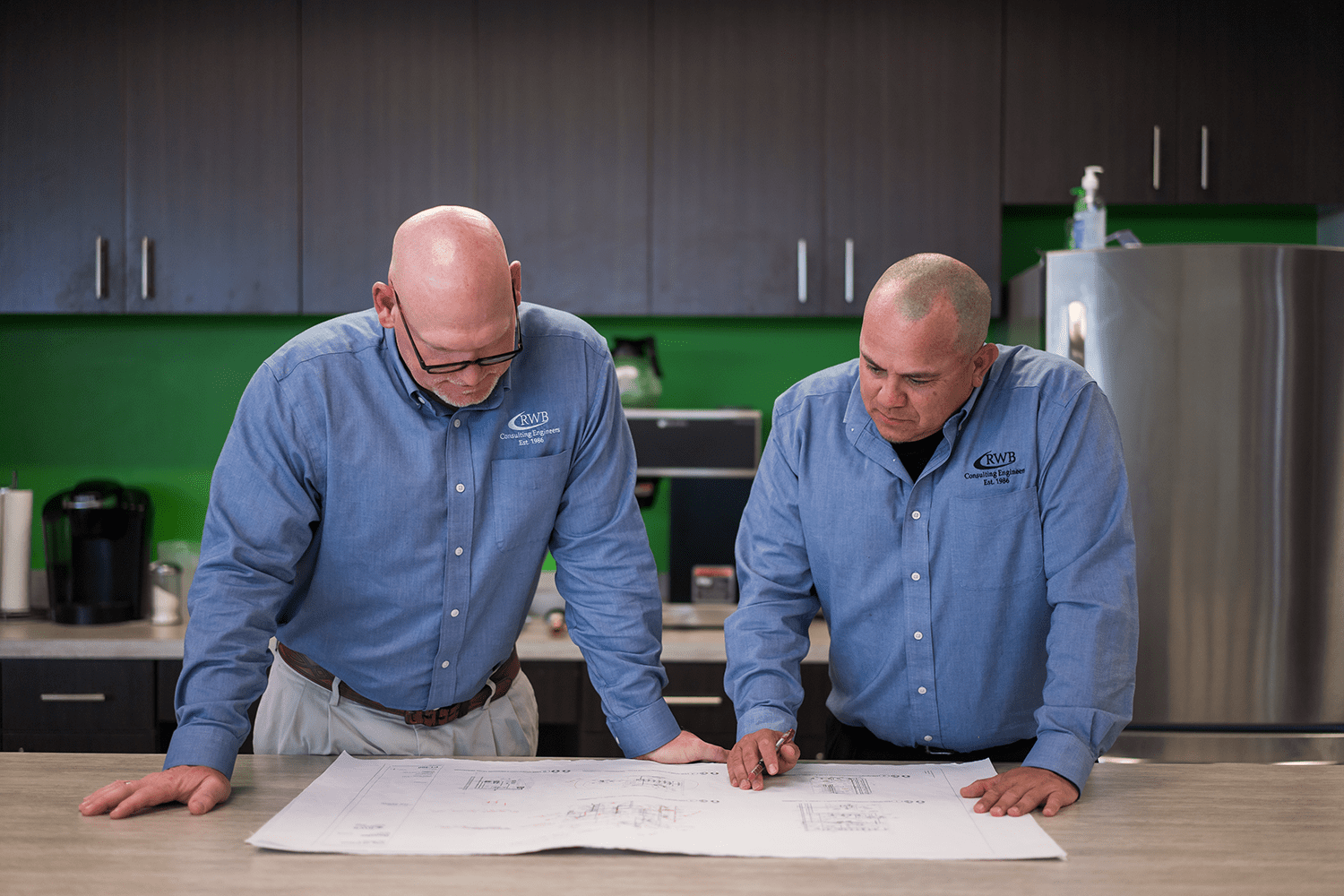 Employees reviewing drawings together